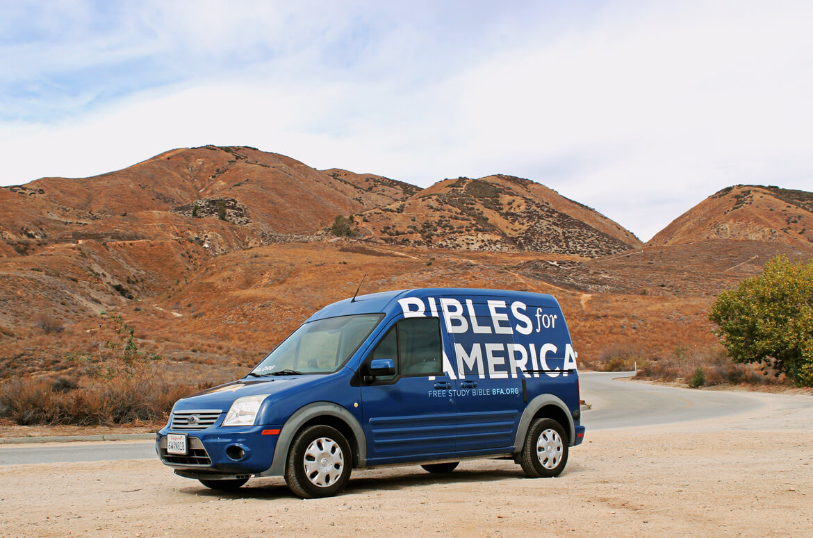 Bright blue vehicle wrap design for Bibles for America in a desert terrain.