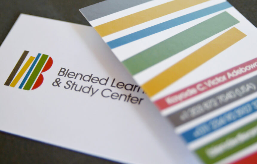 Colorful business card design showing a stack of books for educational company.