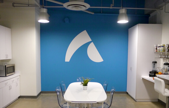 Kitchen at the AppOnboard office with logo on a blue wall.