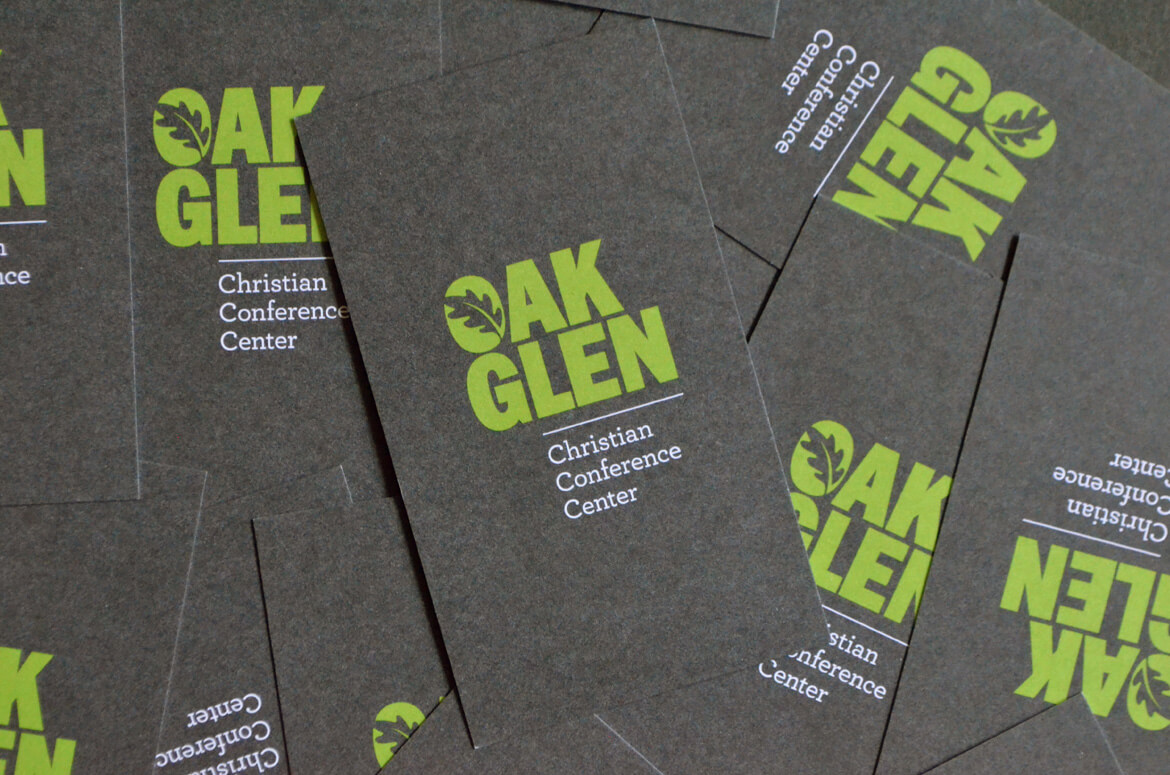 A stack of dark gray business cards printed on textured uncoated paper.