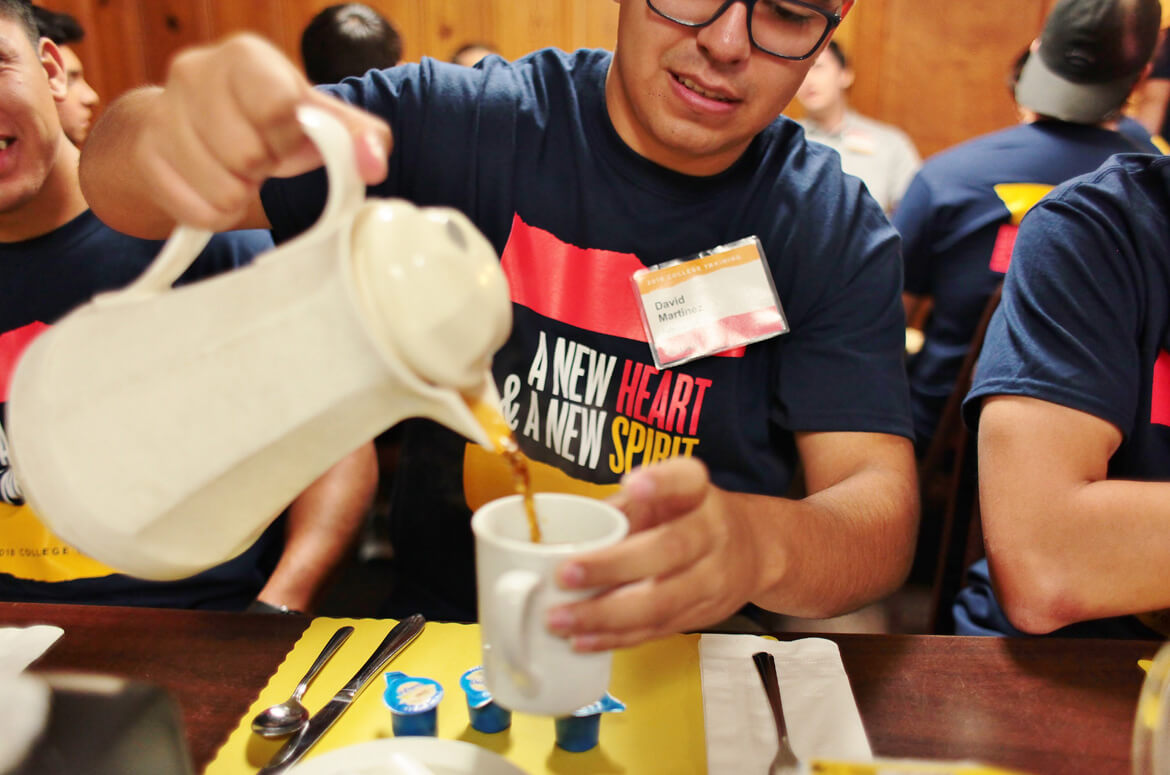 Young man pouring coffee at the 2018 College Training.