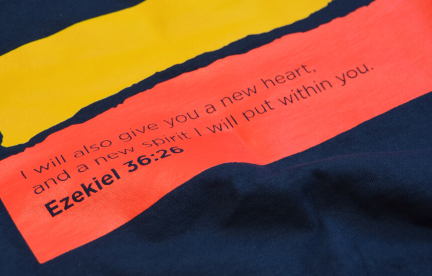 Detail of a Bible verse printed on the back of a T-shirt.