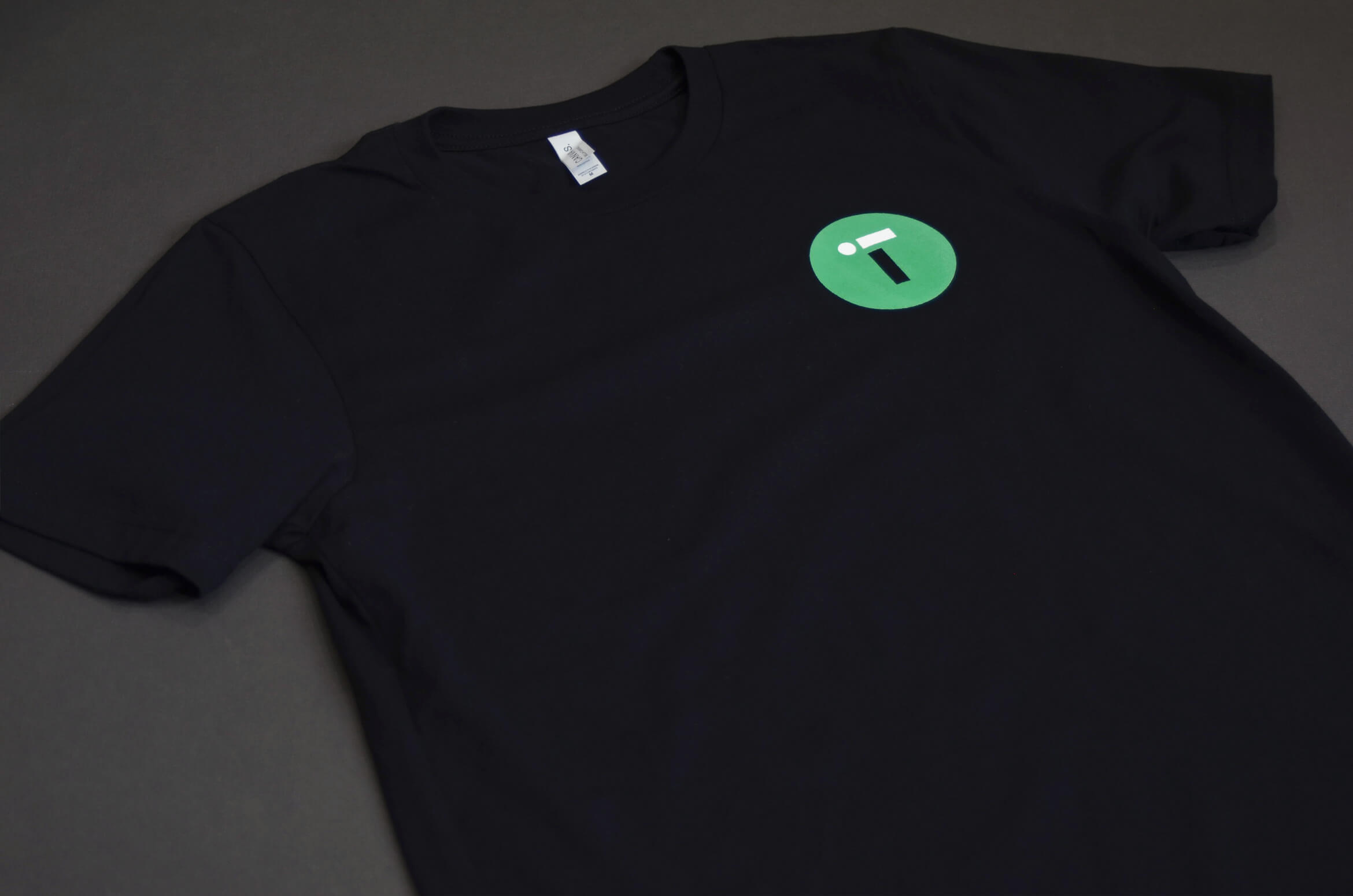 Black T-shirt with IT Retail's circular green logo on the chest pocket.